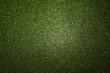 Grüner glitzernder Hintergrund der in der Mitte heller ist