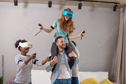 Printed kitchen splashbacks Artist KB Happy red-haired woman in virtual reality headset is riding piggyback on her boyfriend, surrounded by mixed race friends at home. Dating, romantic relationship and virtual reality technology concept.