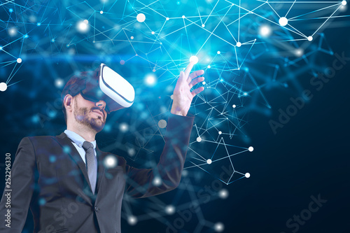 Fotografia, Obraz  Man in VR glasses working with blue network