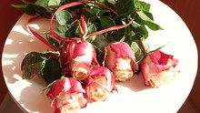 Light Breeze Is Blowing Gently Onto Bouquet Of The Cream-red Roses Lying On A White Table