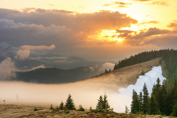Magic spring fogs in Ukrainian Carpathians overlooking the snow-capped mountain peaks from the picturesque mountain valley with tourists in tents.