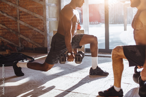 Canvas Print Two multiracial male crossfit sportsmen with naked torso, exercising actively in