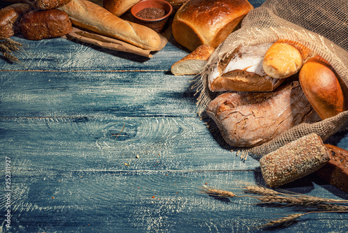 Spoed Fotobehang Bakkerij Different kinds of bread and bread rolls on wood background. Assortment of fresh baked bread, sweet pastries, baked goods, white and rye bread