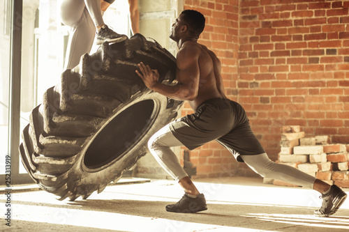 Young muscular woman flipping a tire on hard training with