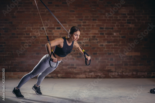 Fotografía  Fitness woman trainin on the TRX in the gym, doing push ups where stabilizing muscles are trained and the whole body is working, which makes such workouts truly functional