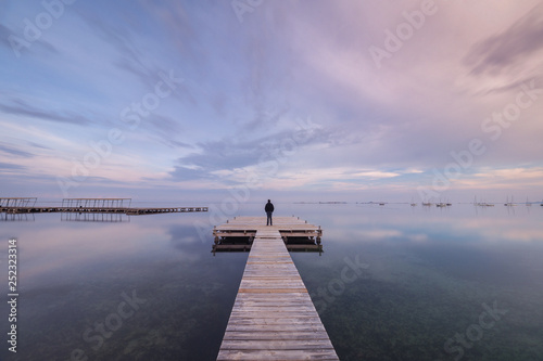 Back view of unrecognizable person standing on long lumber pier near calm sea water on cloudy evening in Spain