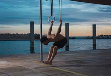 Athletic Man Balancing On Gymnastic Rings