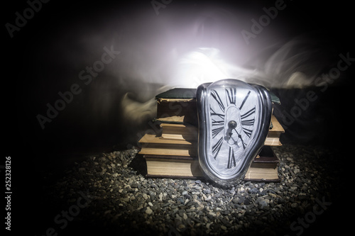 Photo Distorted soft melting clock on a wooden bench, the Persistence of Memory of Sal