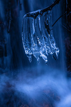 Closeup Twig With Fragile Clean Icicles On Background Of Amazing Waterfall On Cold Winter Day