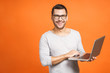Leinwandbild Motiv Confident business expert. Confident young handsome man in casual holding laptop and smiling while standing against orange background.