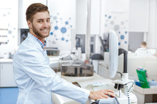 Handsome Young Male Laboratory Technician Operating Computerized Analyzing Machine