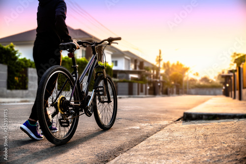 Photo Stands Bicycle Bike at the summer sunset on the tiled road , Exercising of bike on road village background. Cycling down the street to work at summer sunset, sunrise. Bicycle and ecology lifestyle concept. - Image