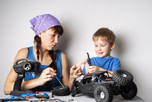 Women In The Men's Work: Mom Helps Her Son With Fixing A Radio-controlled Buggy Model.