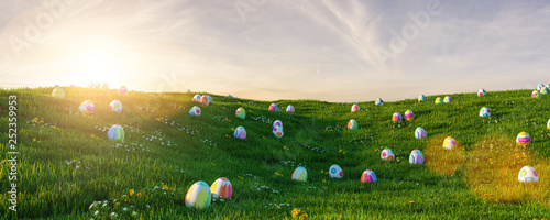 Many colorful easter eggs in the grass of a meadow for easter at sunset Canvas Print