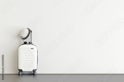 Foto White suitcase with hat and sunglasses  in airport departure lounge