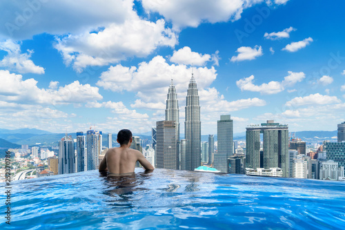 Foto auf AluDibond Kuala Lumpur Back of tourist in a swimming pool on rooftop with Kuala Lumpur downtown view and blue sky. Malaysia travel trip in vacation and holidays concept in Asia. Skyscraper and high-rise buildings at noon.