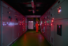 Engineer Checking And Monitoring The Electrical System In Electrical Switch Gear At Low Voltage Motor Control Center Cabinet Room,Electrical Button Switch At Night.