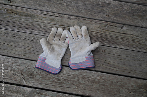Fotografija  Inexpensive cotton and sueded leather work gloves - palms up showing use