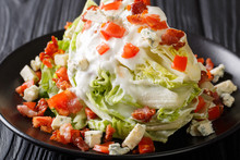 Delicious Classic Wedge Salad Covered In A Tasty Blue Cheese Dressing, Crunchy Bacon, And Fresh Tomatoes Closeup On A Plate. Horizontal