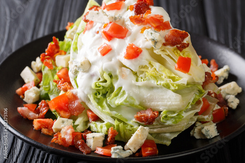 Slika na platnu delicious Classic Wedge Salad covered in a tasty blue cheese dressing, crunchy bacon, and fresh tomatoes closeup on a plate