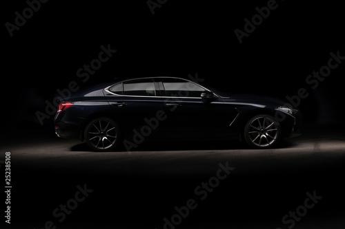 Fototapeta Four-door sport coupe. Silhouette of black sports car with headlights obraz na płótnie