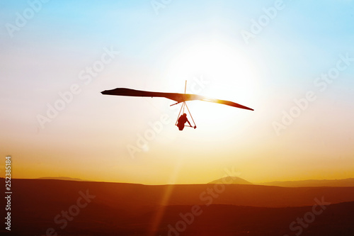 Fotografía  Hang-glider  flight in sky in sunset time over the