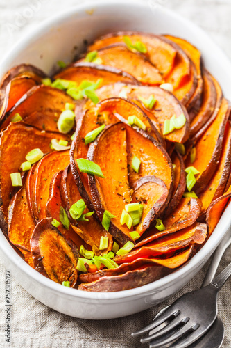 Photo  Baked sliced sweet potato with green onions in white dish.