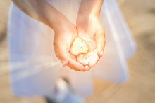 Little Girl Holds A Shining Heart In Her Hands. Light In The Hands Of A Child. Concepts Of Miracle, Magic, Sharing, Giving, Offering, Caring