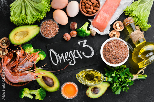 Fototapeta Food with natural vitamin Omega 3. Healthy food: fish, shrimp, broccoli, flax, nuts, egg, parsley. Top view. Free space for your text. On a black background. obraz