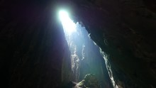 Bright Grotto Ceiling Opening Dark Walls And Narrow Passage