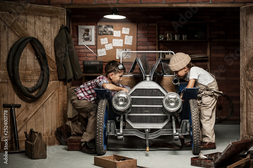 Foto Boys-mechanic with tools in the car in the garage