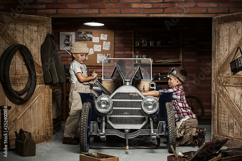 Fototapeta Boys-mechanic with tools in the car in the garage obraz