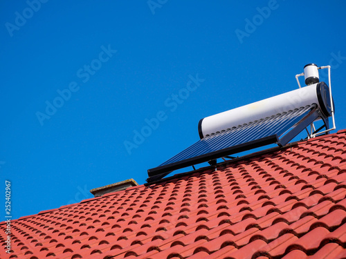 Foto  Solar water heater boiler on rooftop, perfect blue sky  on the background