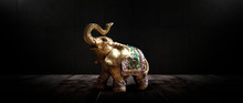 Golden Elephant On A Wooden Table. Dark Room, Light Effect. Beautiful Statuette Of An Elephant On The Background.