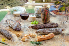 Corsican Specialities Appetizer: Delicatessen, And Cheese Made In Corsica Over A Swimming Pool Panorama Background, With A Glass Of Wine