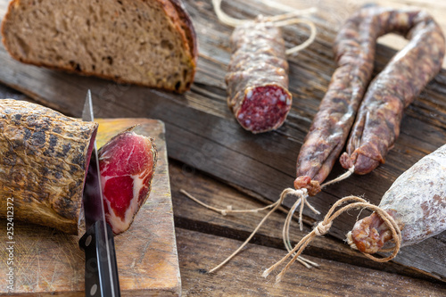 Local wild pork meat , delicatessen, made Corsica France wooden background