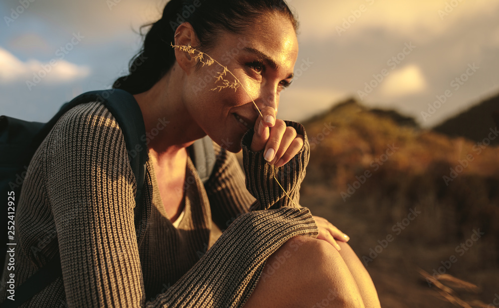 Fototapety, obrazy: Female hiker taking a rest after a country walk