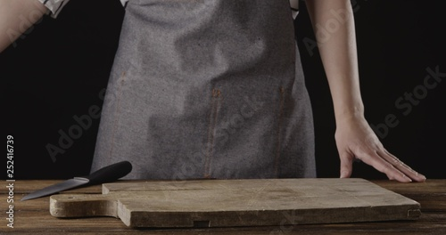 Spoed Fotobehang Gymnastiek Chef in a apron are standing at the table with wooden cutting board on it on a black background.