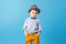 Portrait Of Happy Joyful  Little Boy Isolated On Blue Background. Toddler Child In Hat And Fashionable Suit Smiling And Have A Fun. Copy Space For Text Right Side