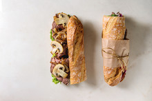 Opened And Tied Beef Baguette Sandwich With Champignon Mushrooms, Green Salad, Fried Onion Over White Marble Background. Flat Lay, Space