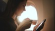 Amazing close-up shot of young relaxed woman using smartphone app and drinking tea on airplane flight sunny window seat.