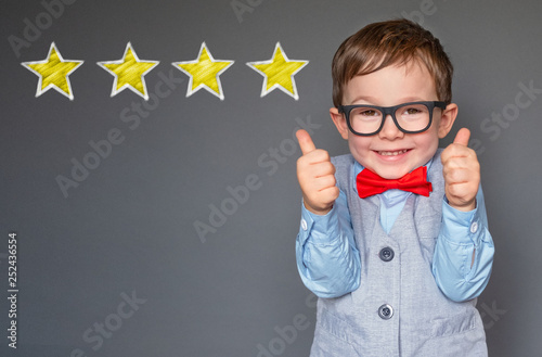 Leinwand Poster Cute little boy giving thumbs up with 4 stars approved