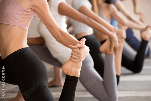 Fotomural  Group of young yogi women practicing yoga, Horse rider pose