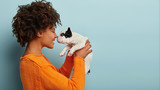 Fototapeta Zwierzęta - Sideways shot of pleased charming young woman has dark skin, curly hairstyle, touches noses with favourite dog, plays with french bulldog, dressed in orange jumper, isolated over blue background