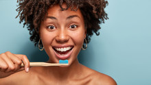 Studio Shot Of Cheerful Dark Skinned Beautiful Woman Holds Toothbrush Near Mouth, Maintains Oral Hygiene, Looks Happily At Camera, Has Bare Shoulders, Stands Indoor In Bathroom Over Blue Studio Wall