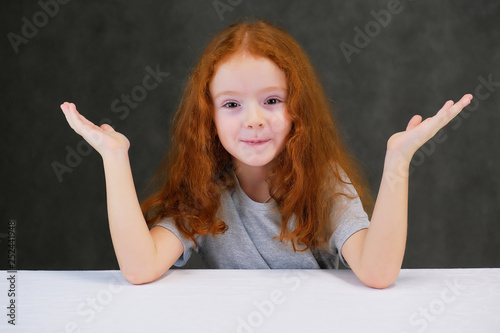 Photographie  Concept portrait of a cute pretty child girl with red hair on a gray background smiling and talking
