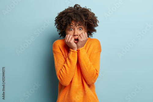 Fotografía  Concerned black young woman shakes from fear, keeps hands near mouth, has nervous facial expression, widely opened eyes, wears orange jumper, isolated over blue background