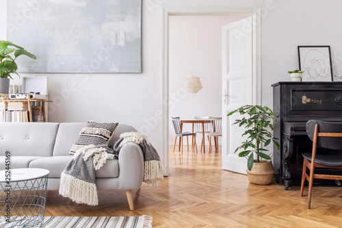 Obraz Modern scandianvian decor of living room with design sofa with elegant blanket, coffee table and bookstand on the white wall. Brown wooden parquet. Concept of minimalistic interior with piano. Mock up - fototapety do salonu
