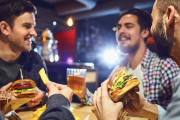 Szczęśliwi przyjaciele jedzą hamburgery, piją piwo w barze.