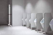Row Of Clean Porcelain Sensor-operated Male Urinals With Partitions In Airport Terminal. Light Public Restroom With White Ceramic Sanitary Fixtures For Urination For Men. Comfort And Hygiene Concept